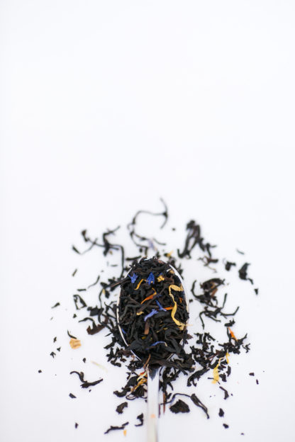 Very dark black tea blended with corn flower petals and yellow marigold petals flow over the silverspoon onto the whtie background