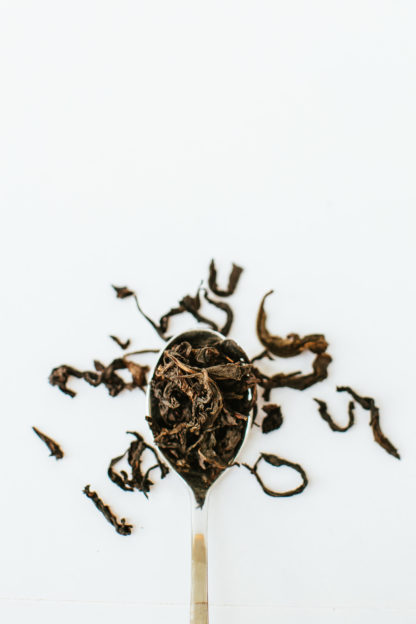 Silver tea spoon overflowing with very long tendril-like tea oolong tea leaves on white background