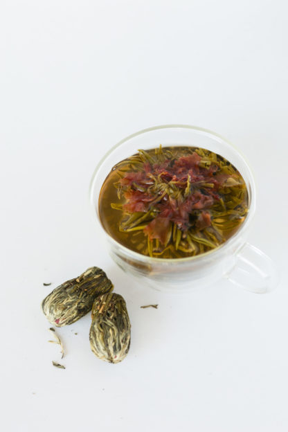 Orange carnation flower in the center of a green and white tea bouquet in the clear cup with oblong teaballs waiting to be steeped on a white background