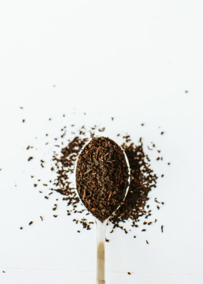 Silver tea spoon overflowing with tightly dried pieces of black tea leaves on white background