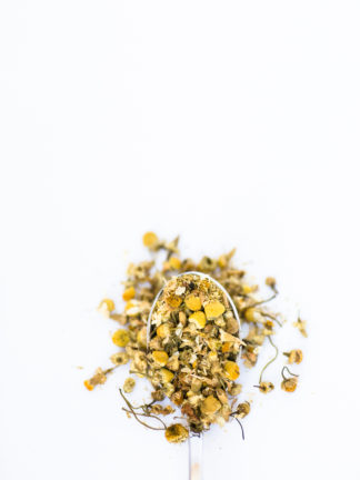 An overflowing scoop of chamomile florets in a silver spoon on white background