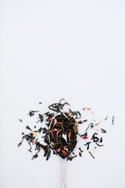 An overflowing silver spoon full of medium length black tea leaves sprinkled with a carnival of naturally colored flower petals on white background