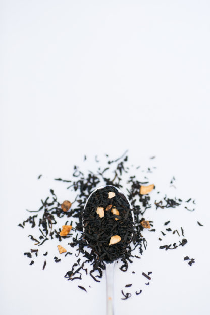 Black tea leaves and dried apricot pieces cascade over the silver spoon onto a white background