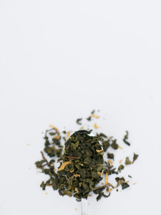 Tightly clumped rich green oolong tea leaves with truffle shavings and yellow flower petals spill over a silver spoon onto a white background
