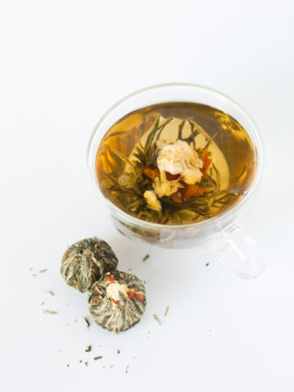 A string of jasmine flowers arch over the red lilly center surrounded by green and white teas in a clear cup with dry tea balls waiting to be steeped all on a white background
