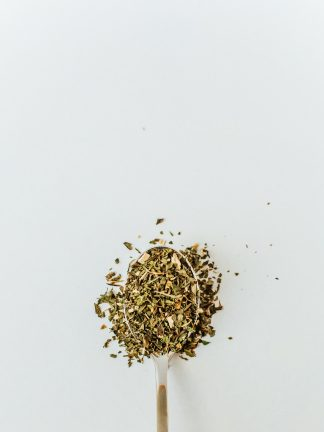 Tan colored shredded ginseng root blended with bright green chopped peppermint leaves overflow the silver spoon onto a white background