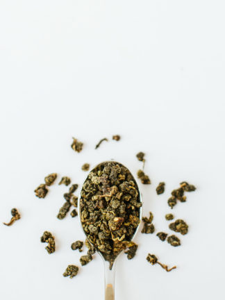 Jade green clumped oolong tea leaves resemble tea gravel spilling over the silver spoon onto the white background
