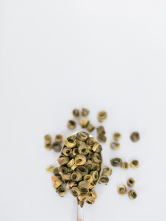Light green and yellow tea leaves wrapped around a hollow center spilling over the silver spoon onto the white background
