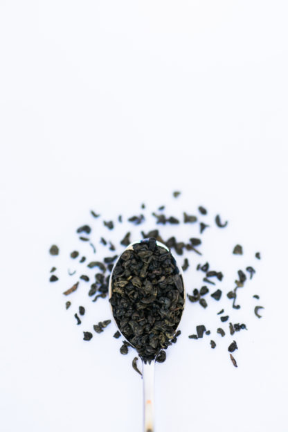 Tightly clumped green tea leaves spilling over the silver spoon onto the white background