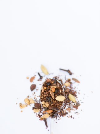 Dark red rooibos needles blended with cloves, cardamom pods, and cinnamon bark chips spill over the silver spoon onto a white background