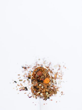 Dried orange & red rose hips, with clove and cinnamon bark chips sprinkled among dark red rooibos needles spill over the spoon onto a white background