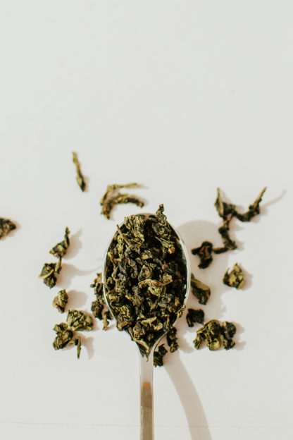 Vivid green clumps of oolong tea leaves spill over the silver spoon onto the white background