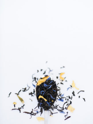 Bright yellow safflowers and dark blue corn flowers blended with dark black tea overflowing a silver spoon onto a white background