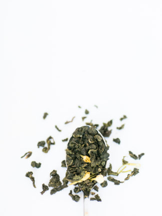Jade green classic clumped oolong tea leaves with marigold flower petals spill over the silver spoon onto the white background