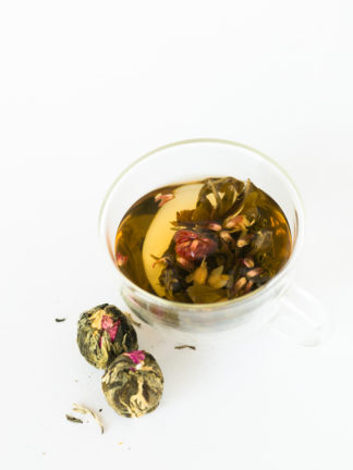 A bouquet of pink globe aramath flowers are cradled by green and white tea leaves in a clear glass cup with the dry blooming teas waiting to be steeped all on a white background