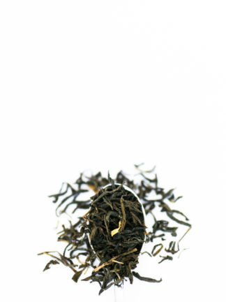 Long and dark green tea leaves are sprinkled with pieces of cream colored jasmine flower petals and flow over the silver spoon onto the pure white background