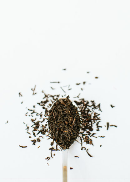 Medium black tea with red highlights fill the silver spoon and spill onto the white background