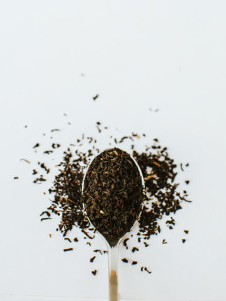 Fine dark tea leaf pieces overflow the silver spoon onto white background