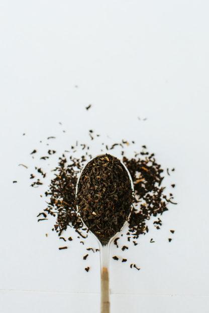 Fine dark tea leaf pieces overflow the silver spoon onto white background