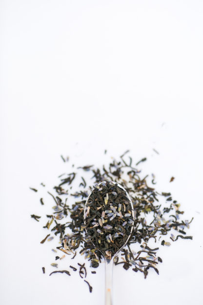 Purple lavender florets mix with dark black tea leaves spilling over the silver spoon onto the white background