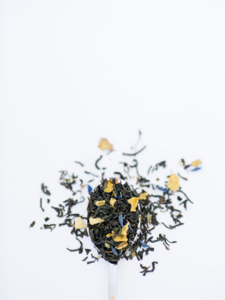 Bright chopped and dried lemon peel mixed with green mint fill the silver spoon and flow onto the white background