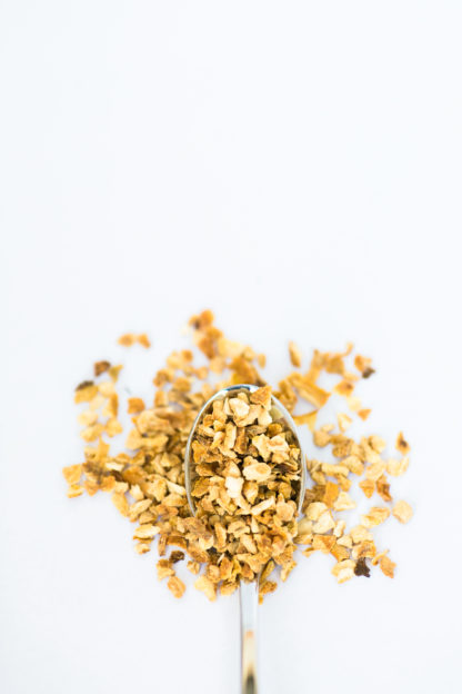 Bright yellow finely chopped lemon peel pieces pour from the silver spoon onto a white background