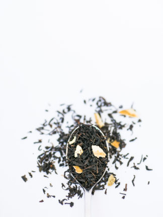 Yellow lemon grass and lemon peal blended with dark brown black tea in silver spoon spilling onto a white background