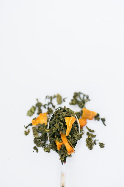 Dried yellow peach pieces are sprinkled among the dark green clumped tea leaves overflowing the silver spoon onto the white background