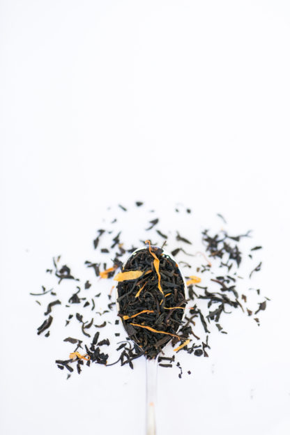Dried apple and safflower petals blended with dark brown black tea in silver spoon overflowing onto white background