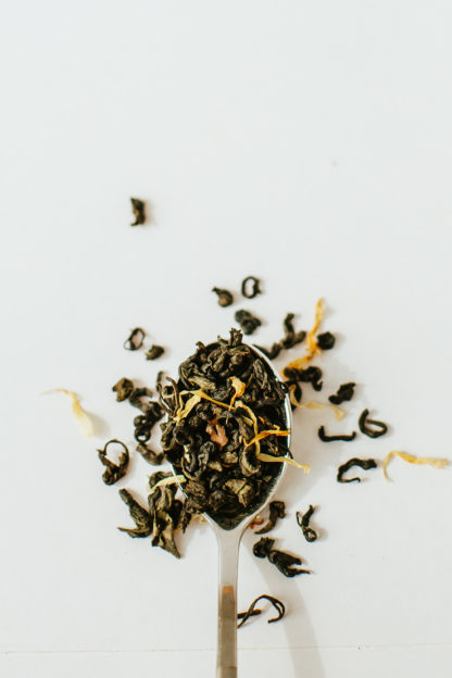 Twisted dark green tea leaves and yellow shredded mango spill over onto a white background