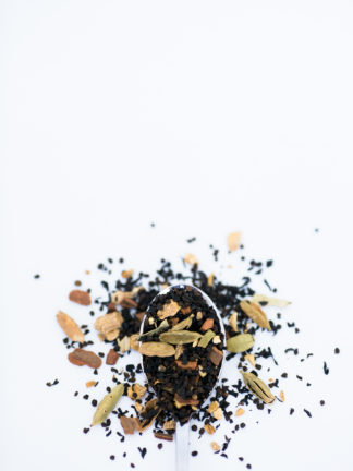 Filely chopped black tea leaves mix with green coriander pods, cloves, and rusty cinnamon bark spill onto a white background