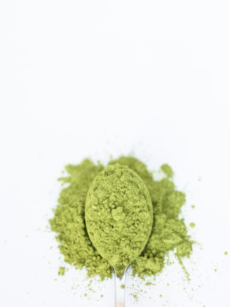 Brilliant green tea powder spilling over a silver spoon onto a white background