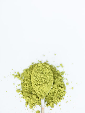 Bright green and very finely ground tea powder spills over the silver spoon onto the pure white background