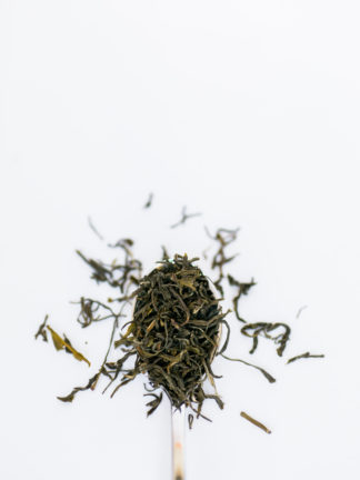 Thin dark tea leaves like twisted threads overflow the spoon onto the white background