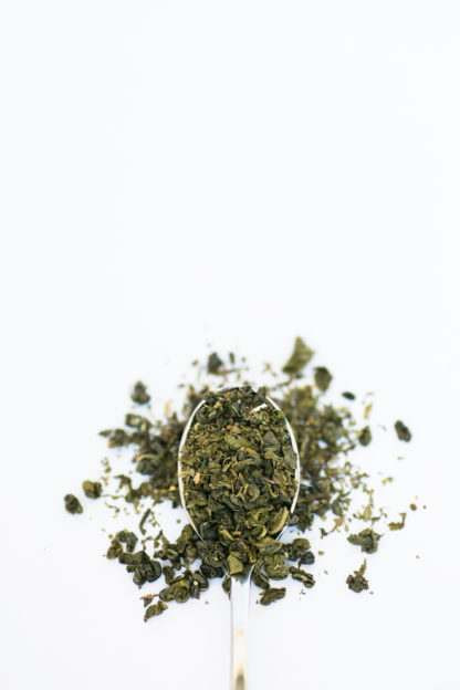 Bright green chopped mint leaves are blended with darker green classically clumped gunpowder green tea overflowing the silver spoon onto the pure white background
