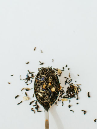 Dark green black tea leaves sprinkled with orange peel and dark blue corn flowers in silver spoon on white background