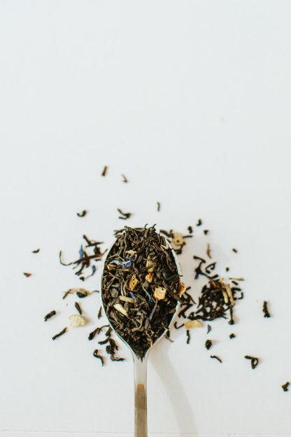 Dark green black tea leaves sprinkled with orange peel and dark blue corn flowers in silver spoon on white background