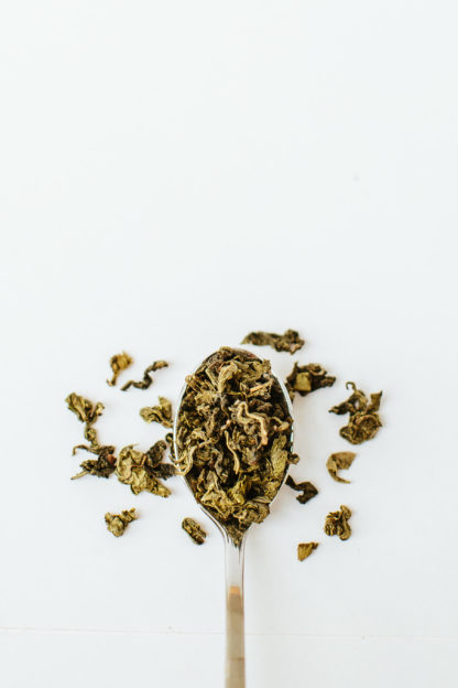 Variegated dark green and light green clumped oolong tea leaves overflow the silver spoon onto a white background