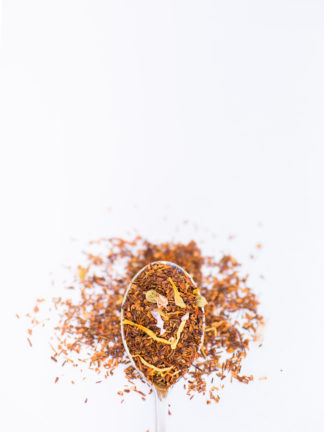 Bright yellow safflower and marigold, blue mallow flower and cornflower petals blended into dark red rooibos needles overflow a silver spoon onto a white background