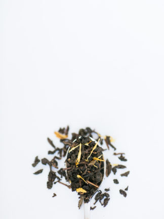 Yellow marigold flower petals are sprinkled among the clumped classic oolong tea leaves overflowing the silver spoon onto the white background