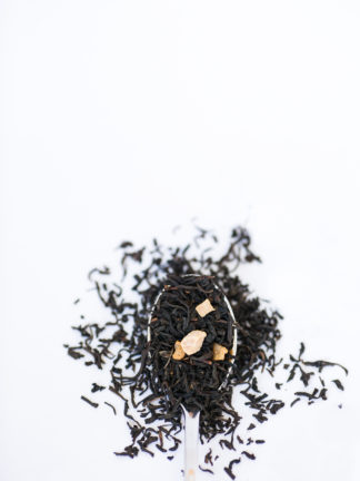 Dark brown black tea leaves dotted with dried peach pieces spill over the silver spoon onto the white background