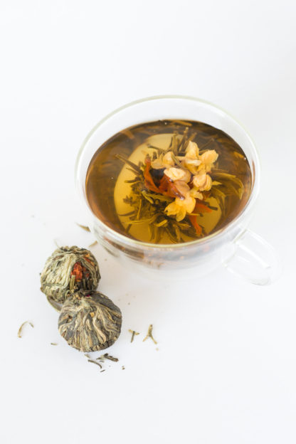 Red Lily and light yellow jasmine flowers center the green and white tea wrapped ball unfurls light gold in hot water