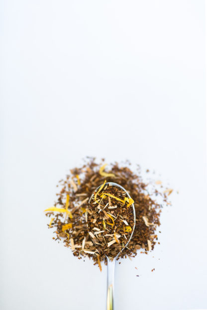 Bright yellow shredded dried peach pieces blend with dark red chopped rooibos needles overflow onto white background