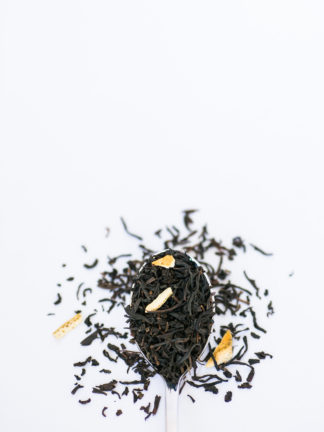 Dark brown black tea leaves blended with dried apply and lemon peel spill from the silver spoon onto the white background