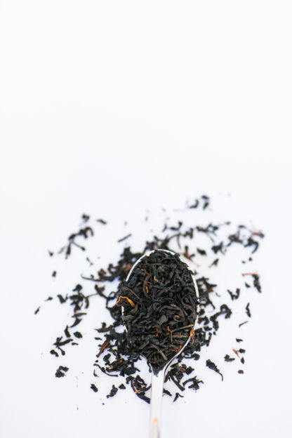 Small black tea leaves sprinkled with orange safflower petals overflow the spoon onto a white background