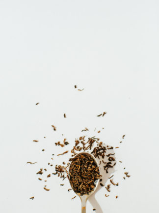 Dark red fermented black tea leaves overflow a silver spoon onto a white background