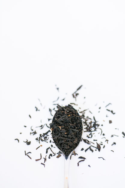Dark brown black tea leaves overflow the silver spoon onto the white background