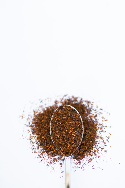 Deep red coarsely ground rooibos needles spill over the silver spoon onto a white background