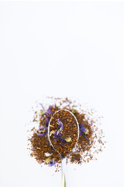 Dark chopped rooibos needles blended with dark purple corn flowers and bright yellow safflower petals fill a silver spoon