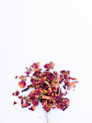A spectrum of dried red rose petals ranging from dark red to orange red pour out of a silver spoon onto a white background